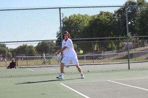 Junior John Harrington returns a forehand in a match against Bellevue West. Photo by David Church.