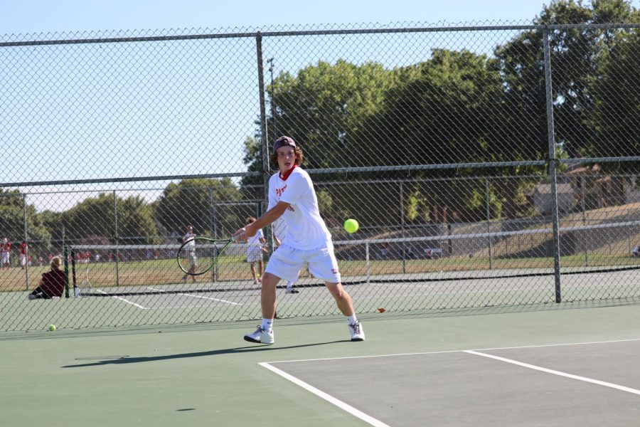 Junior+John+Harrington+returns+a+forehand+in+a+match+against+Bellevue+West.+Photo+by+David+Church.