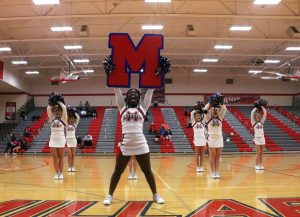 Senior Paola Kangni-Soupke holds up an 'M' as she performs the team's cheer at halftime. Photo by Carly Barkus.