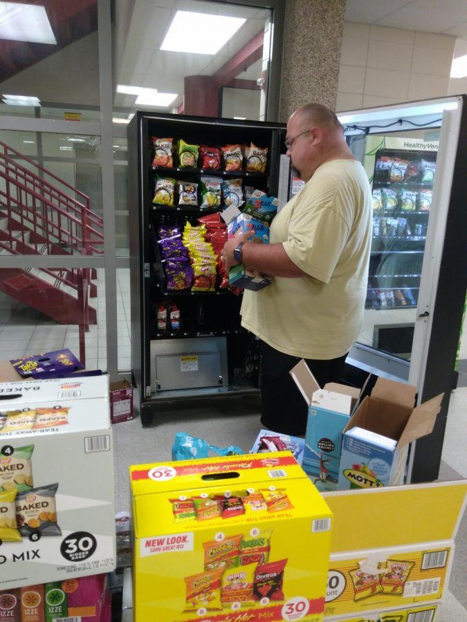 Nick Stuto of J&B Enterprises restocks the vending machine in the 100 commons after school. Stuto says he is coming twice a week now to restock. The most popular item is Takis, he said. Photo by Christine Kaldahl